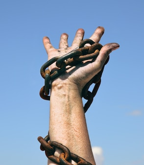 Right female hand holds a rusty chain
