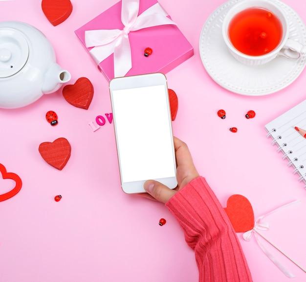 분홍색 스웨터에 오른쪽 여성의 손은 흰색 스마트 폰을 들고있다