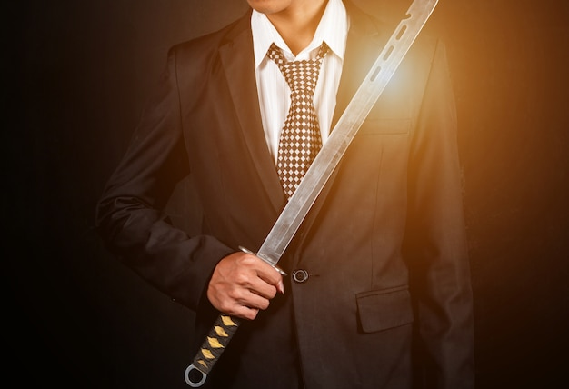 The right hand of a businessman holding a sword on a dark background.
