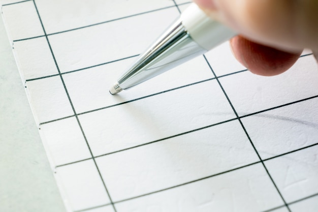 Right hand holding a pen signing on paper