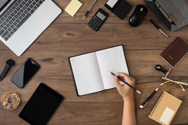 Right hand holding pencil on empty notebook list with office accessories on table flat lay.
