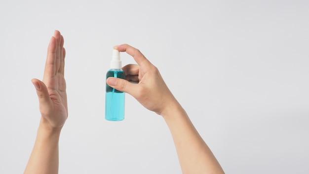 오른손은 알코올 스프레이를 들고 흰색 배경에 왼손을 향하고 있습니다.