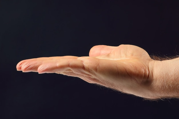 Правая рука мужчин на темном фоне