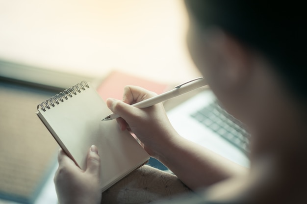 Right-handed woman writing on small notepad
