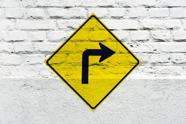 右折:落書きのように白い壁に交通標識がスタンプされています