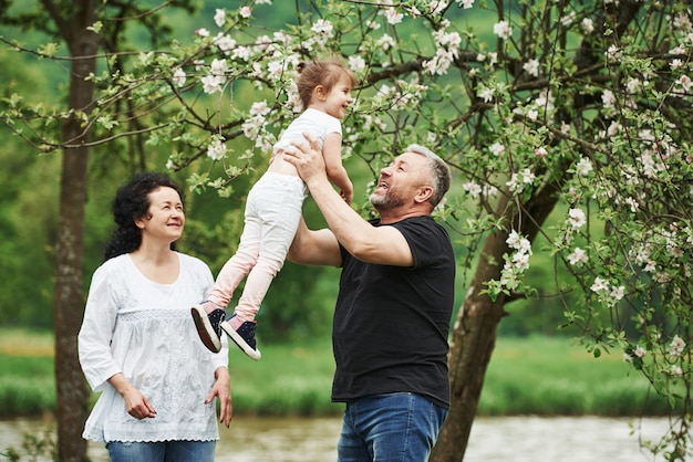 바로 공중에. 손녀와 함께 좋은 주말을 야외에서 즐기는 명랑 커플. 좋은 봄 날씨