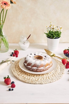 Ring cake with fruits and powder on a white table with white surface