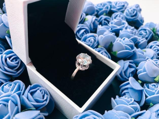 Кольцо для предложения руки и сердца украшено декоративными цветами. день святого валентина фон.