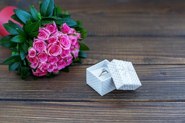 Кольцо в подарок и букет роз.
