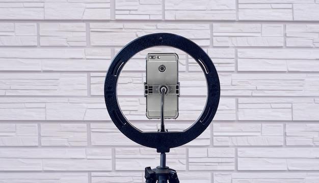 Кольцевая лампа и смартфон у стены