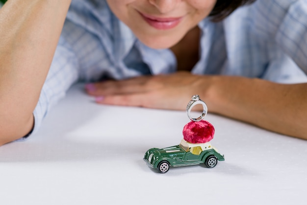 Ring on a toy retro car and an admiring woman