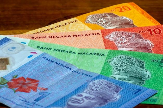 Деньги ринггит малайзии лежат на деревянном столе, в мелком фокусе