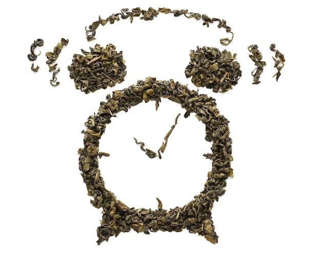 白で隔離される乾燥ウーロン茶葉で作られた目覚まし時計の形をリンギング。発酵した中国の緑茶。