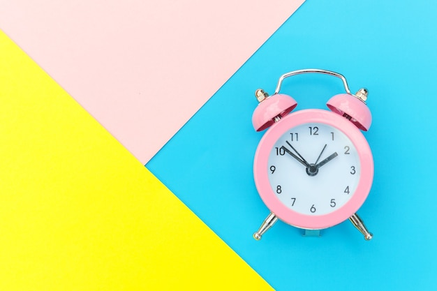 Ringing twin bell classic alarm clock isolated on blue yellow pink pastel colorful geometric table. rest hours time of life good morning night wake up awake concept. flat lay top view copy space.