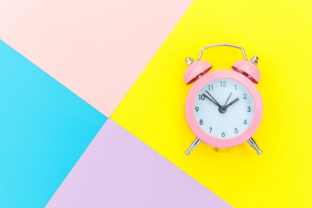 Ringing twin bell classic alarm clock isolated on blue yellow pink pastel colorful geometric wall. rest hours time of life good morning night wake up awake concept. flat lay top view copy space.