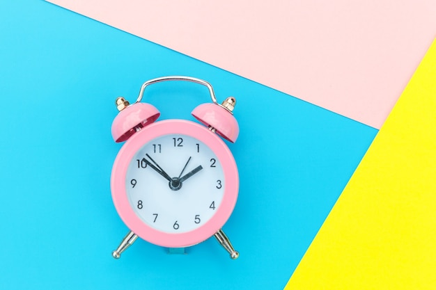 Ringing twin bell classic alarm clock isolated on blue yellow pink pastel colorful geometric