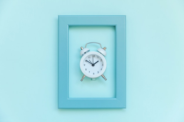Ringing twin bell vintage alarm clock in blue frame isolated