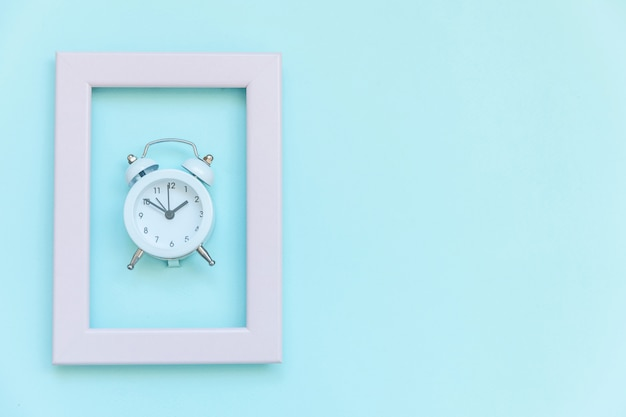 Ringing twin bell vintage alarm clock in pink frame isolated on blue pastel colorful trendy background