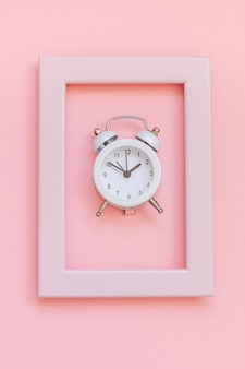 Ringing twin bell vintage alarm clock in pink frame isolated on pink pastel surface