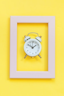 Ringing twin bell vintage alarm clock in pink frame isolated