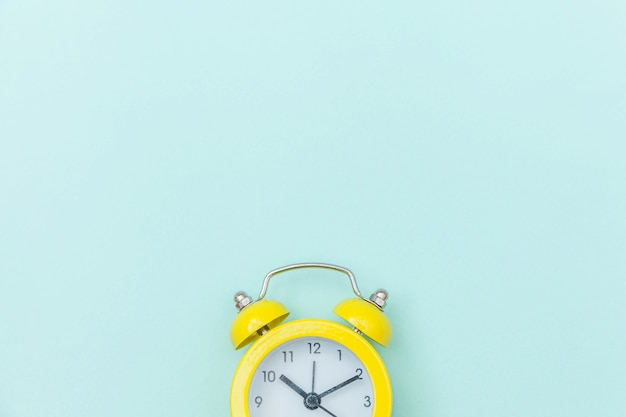 Ringing twin bell vintage classic alarm clock isolated on blue colorful trendy pastel background. rest hours time of life good morning night wake up awake concept. flat lay top view copy space.