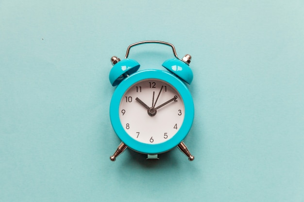 Ringing twin bell vintage classic alarm clock isolated on blue pastel colorful trendy background. rest hours time of life good morning night wake up awake concept
