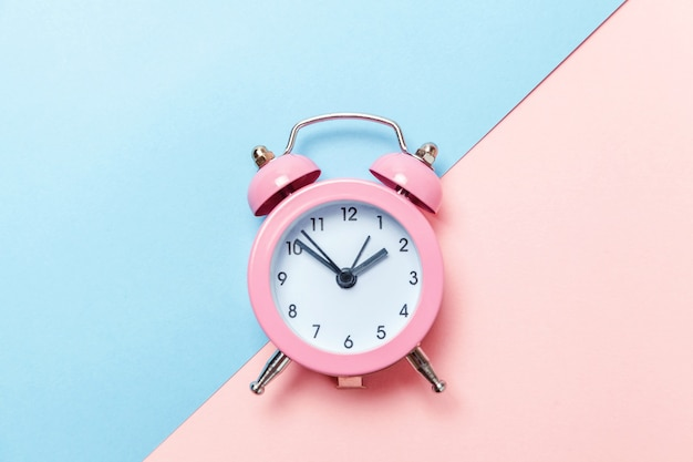 Ringing twin bell vintage classic alarm clock isolated on blue pink pastel colorful trendy