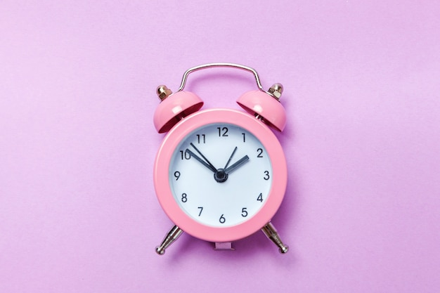 Ringing twin bell vintage classic alarm clock isolated on purple violet pastel colourful