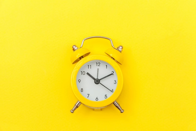 Ringing twin bell vintage classic alarm clock isolated on yellow colourful trendy modern background. rest hours time of life good morning night wake up awake concept. flat lay top view copy space.