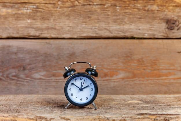古いぼろぼろの素朴な木製の背景にツインベルヴィンテージクラシック目覚まし時計を鳴らします
