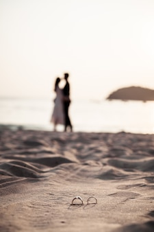 Rings on beach with bride and groom