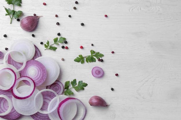 링은 흰색 나무 테이블에 허브와 향신료를 넣은 붉은 양파로 자른다. 채소. 평면도