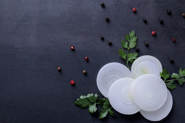 Rings cut into white onions with herbs and spices on a dark blue background. vegetables. top view