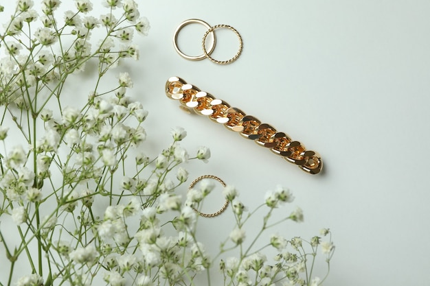 Rings, hair clip and gypsophila on white background