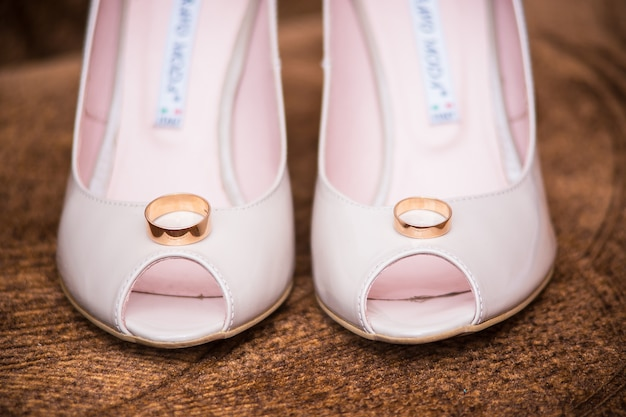 Rings lie in the shoes of the bride