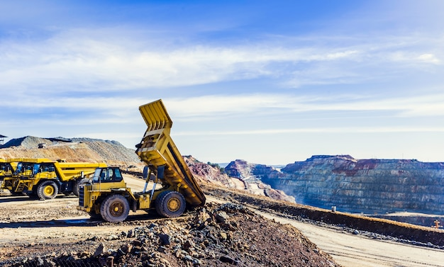 Riotintoの露天掘り鉱山で鉱石の荷を傾けるダンプカー