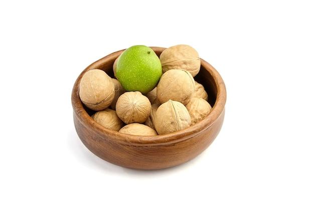Спелые и зеленые грецкие орехи в деревянной миске, изолированные на белом фоне