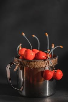 Спелые и сочные вишни в старой металлической чашке на темном деревенском фоне