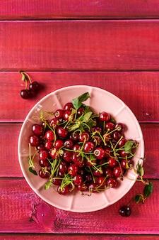 Спелые и сочные вишни на розовой тарелке