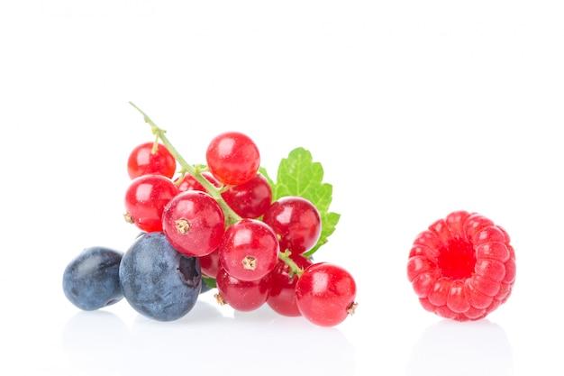 ブルーベリーとラズベリーの白い背景で隔離の熟したジューシーな赤スグリの果実。