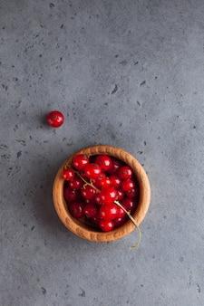 회색 질감 표면에 나무 그릇에 잘 익은 육즙 붉은 건포도