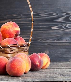 かごの中の熟したおいしい桃は、黒い木製のテーブルの上に立つ