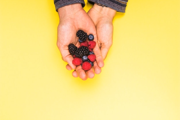 Ripe appetizing raspberry blackberry and currant in hands on yellow surface