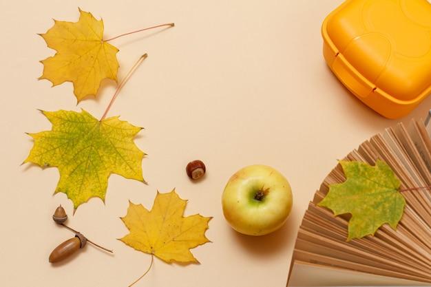 熟したリンゴ、本、プラスチック製のお弁当箱、乾燥した黄色のカエデの葉、ベージュの背景にドングリ。上面図。