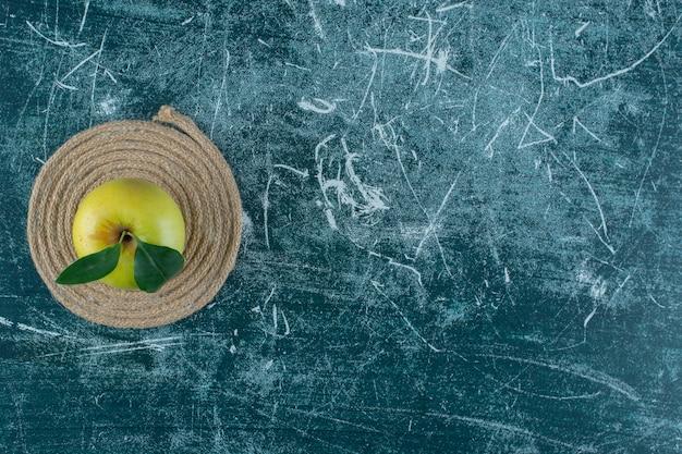 Спелое яблоко на подставке, на мраморном столе.