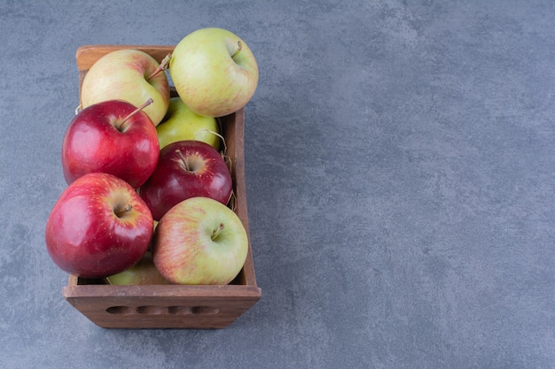 Ripe apples in box on the dark surface