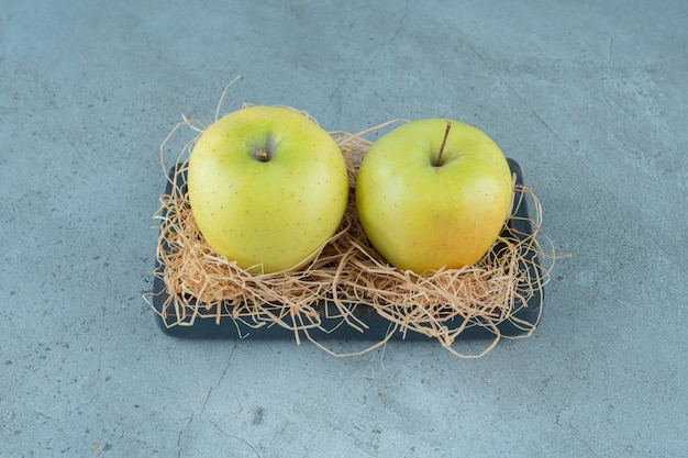 Ripe apples on dry straw and on a board , on the marble background. high quality photo