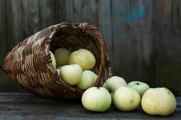 Спелые яблоки в плетеной корзине на деревянном столе. новый урожай и витамины от природы. крупный план.
