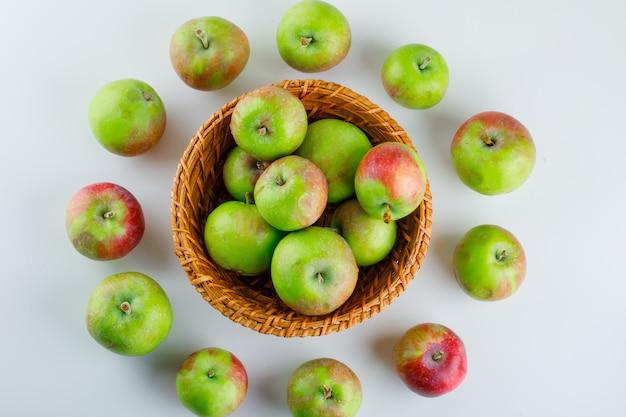Спелые яблоки в плетеной корзине на белом. плоская планировка.