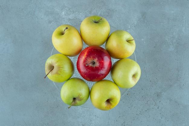 大理石の背景に、ガラスの台座に熟したリンゴ。高品質の写真